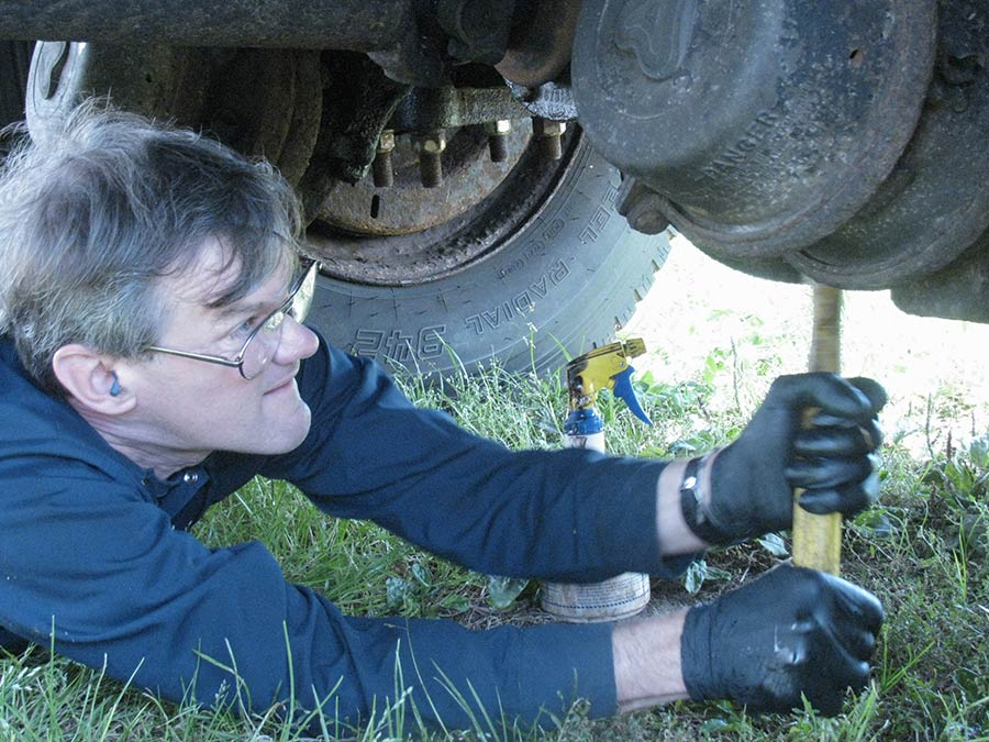 one of the men staff mechanics working underneath a truck