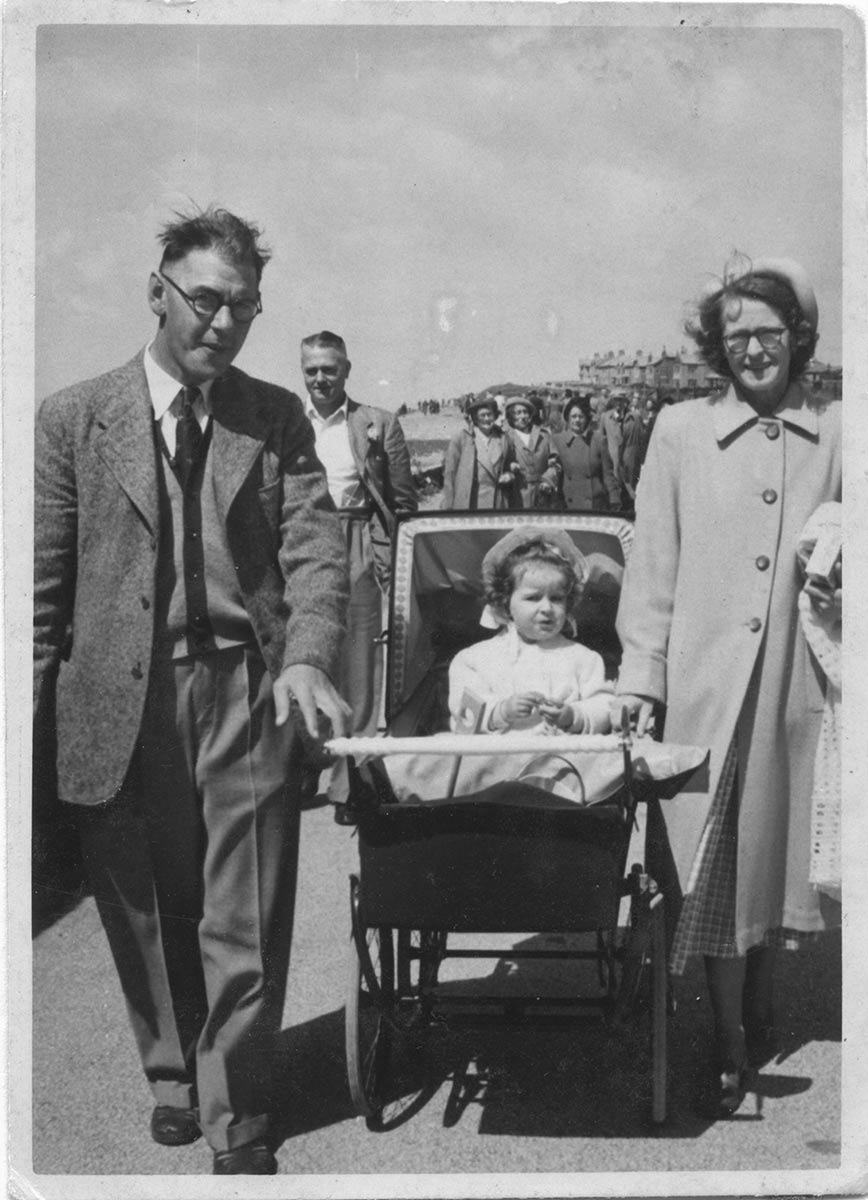 Helen, a toddler, in a pram, with her mother and father on either side